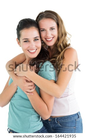 Side view portrait of a young female embracing her friend over white background