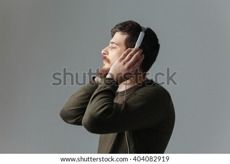 Side view portrait of a young man listening music in headphones over gray background - stock photo
