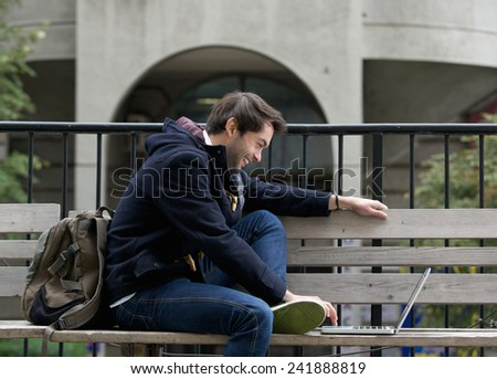 Side view portrait of a young man sitting on bench smiling at laptop  - stock photo
