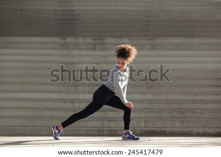 Side view portrait of a young woman stretching leg muscles outdoors - stock photo