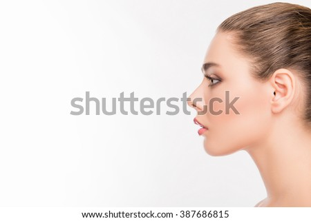Side view portrait of attractive woman's face on white background - stock photo