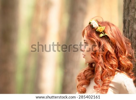 Side view portrait of beautiful redhead woman with gentle flower wreath in hair in the forest, fashion look, gorgeous hairstyle - stock photo