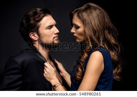 Side view portrait of beautiful sensual couple in elegant clothes posing on black
