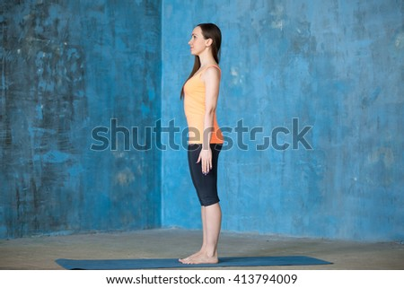 Side view portrait of beautiful young woman dressed in bright sportswear enjoying yoga indoors. Yogi girl working out in grunge interior with textured blue wall. Standing in tadasana. Full length - stock photo