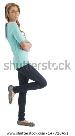 Side view portrait of beautiful young woman with arms crossed leaning over white background - stock photo