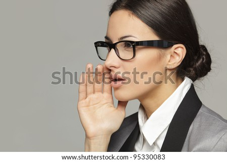 Side view portrait of business woman  calling out to someone over grey background - stock photo