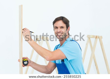 Side view portrait of carpenter marking on wood over white background - stock photo