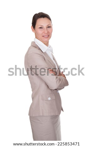 Side view portrait of confident businesswoman standing arms crossed against white background