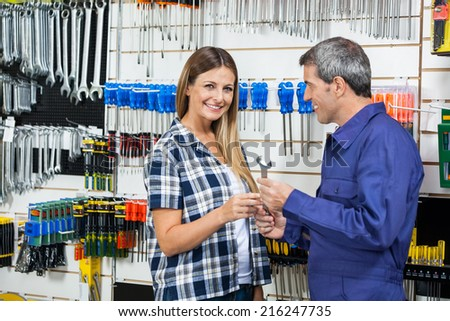 Side view portrait of female customer receiving wrench from customer in hardware shop - stock photo