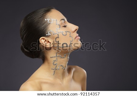 Side view portrait of female with beauty crystal puzzle on her face