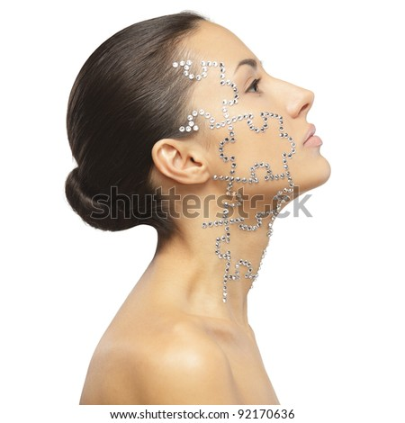 Side view portrait of female with beauty crystal puzzle on her face, isolated on white background