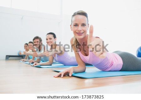 Side view portrait of fit class gesturing thumbs up at fitness studio