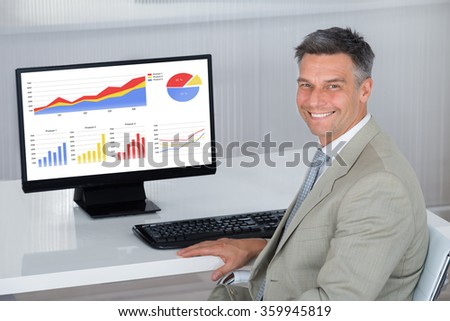 Side view portrait of happy businessman analyzing financial graphs on computer in office