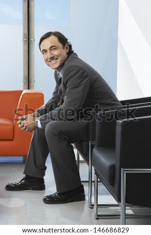 Side view portrait of happy businessman sitting in office lobby - stock photo