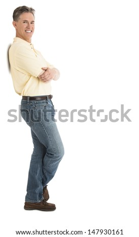Side view portrait of happy man in casuals standing arms crossed over white background - stock photo