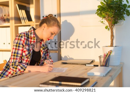 Side view portrait of interior designer writing new project, sitting at workplace. Young smart female student reading and studying university paper. - stock photo