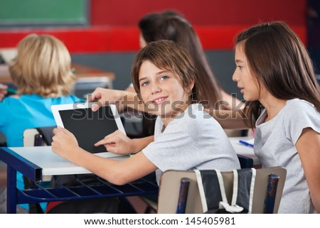Side view portrait of little boy with girl using digital tablet at desk in classroom - stock photo