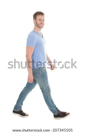Side view portrait of man in casuals walking over white background - stock photo