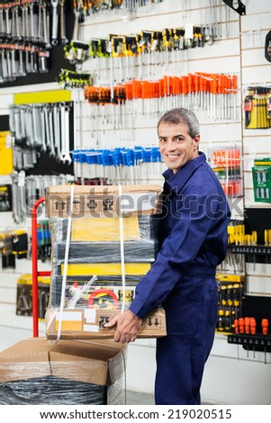Side view portrait of mature worker keeping tool package on trolley in hardware shop