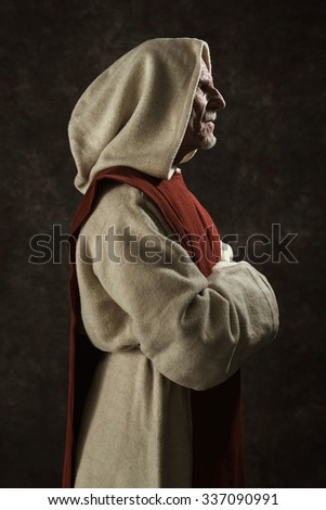Side view portrait of monk. Studio shot against dark wall. - stock photo