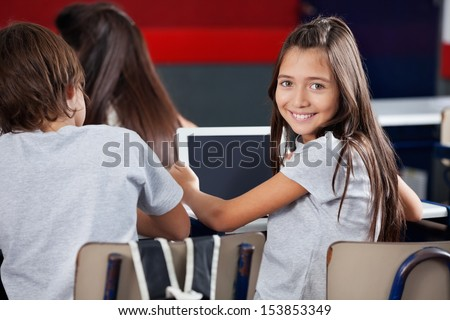 Side view portrait of schoolgirl holding digital tablet at desk in classroom - stock photo