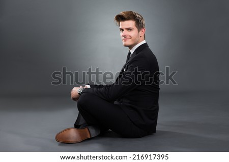 Side view portrait of smiling businessman sitting isolated over gray background - stock photo