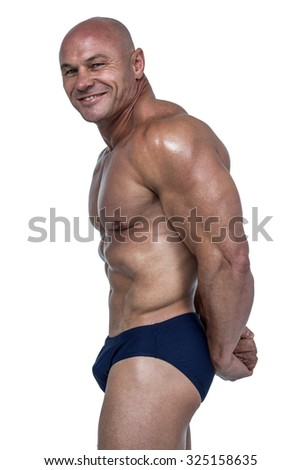 Side view portrait of smiling muscular man against white background - stock photo