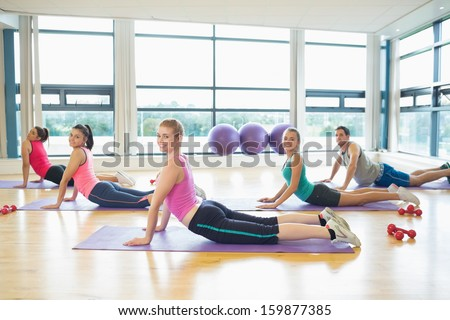 Side view portrait of trainer with class doing the cobra pose in bright fitness studio - stock photo