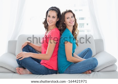 Side view portrait of two smiling young female friends sitting back to back in the living room at home