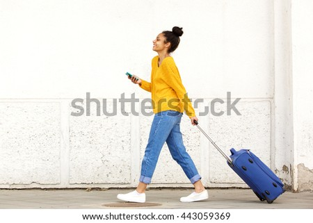 Side view portrait of woman traveler with luggage and mobile phone on city street