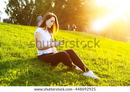Side view portrait of young attractive girl listen to music with a smart phone in the city park. Blurred background with copy space area for a text. - stock photo