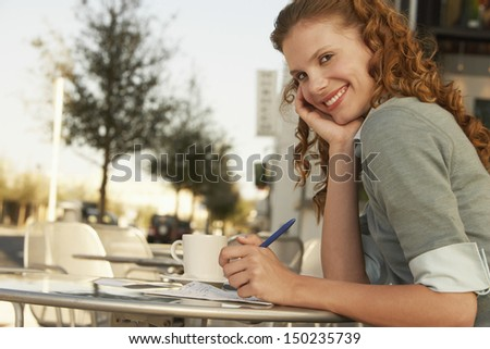 Side view portrait of young businesswoman holding pen at outdoor cafe - stock photo