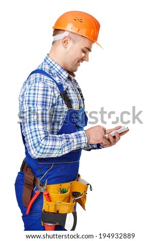 Side view portrait of young male construction worker with smartphone wearing protective clothes, helmet and tool belt isolated on white background - stock photo