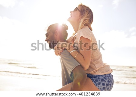 Side view portrait of young man carrying his girlfriend on his back at the beach. Man piggybacking girlfriend at seashore on sunny day. - stock photo