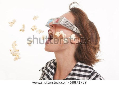 Side view portrait of young woman with 3D glasses and popcorn in the air - stock photo