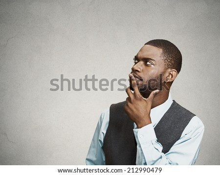 Side view portrait young, puzzled business man thinking, deciding about something, finger on lips, looking up, confused isolated grey wall background with copy space. Emotion facial expression feeling - stock photo