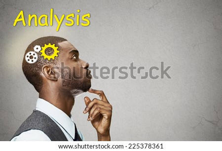 Side view portrait young puzzled business man thinking deciding  finger on chin looking up gear mechanism over head isolated grey wall background copy space. Emotion facial expression perception - stock photo