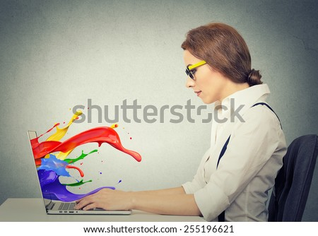 Side view profile attractive happy young business woman working on laptop computer colorful splashes coming out of screen liquid effect isolated grey wall background. Positive face expression vision  - stock photo