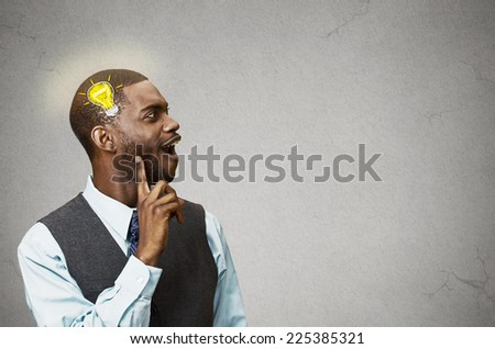 Side view profile headshot happy man thinking found solution for problem isolated grey wall background with copy space light bulb. Human face expression emotion feeling body language perception iq - stock photo