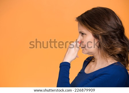Side view profile portrait middle aged woman covers pinches her nose with hand looks with disgust, something stinks bad smell situation isolated orange background. Human face expression body language - stock photo