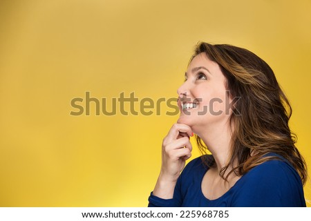 Side view profile portrait thoughtful happy woman smiling looking up daydreaming isolated over yellow background. Positive human face expressions, emotions, feelings, perception  - stock photo
