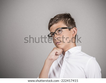 Side view profile portrait young puzzled man thinking, deciding about something, chin on fist looking up pensive isolated grey wall background with copy space. Human emotion facial expression feeling - stock photo