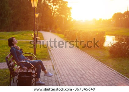 Side view seated woman on the bench enjoying nature in sunny day outdoors, charming young girl relaxing in the summer park, female student relaxing at campus, flare sun light - stock photo