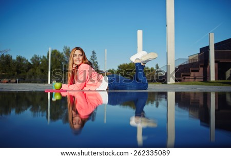 Side view shot of a young trendy woman leaning in the park and enjoying the sunshine feeling so happy, relaxing girl enjoy outdoors at beautiful day, student having class break at campus - stock photo