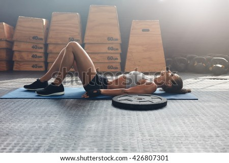 Side view shot of fitness woman resting on exercise mat with a heavy weight plate on floor. Female athlete lying on her back after a gym workout - stock photo