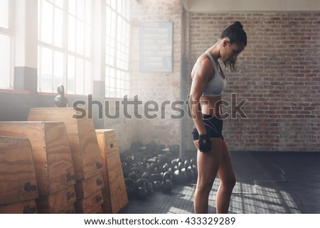 Side view shot of muscular young female athlete in sportswear standing at the gym. Fitness woman preparing herself for the intense workout at gym. - stock photo