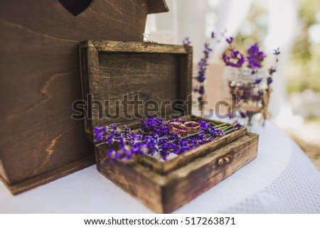 Side view shot of two gold wedding rings on purple flowers in old rustic wooden box for wedding ceremony.  Festive decoration for wedding celebration. Horizontal color photo.