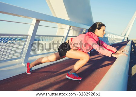 Side view shot of young athletic female dressed in sportswear doing stretching exercise outdoors in summer evening, fit woman with perfect body working out, sporty girl having fitness training outside - stock photo