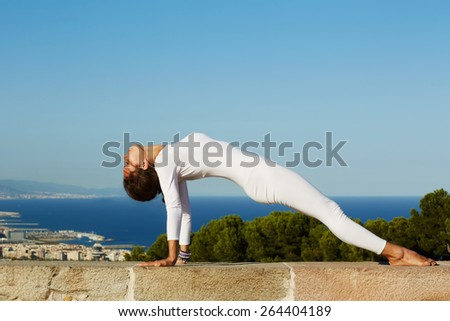 Side view shot young woman with perfect strong body practicing yoga on a sunny day with amazing sea view on background, woman seeking enlightenment through meditation, stretching exercise yoga pose - stock photo