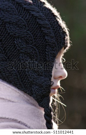 Side view sillouette of female child wearing a winter hat. Sunlight accents the barely visible features